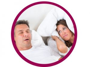 man snoring woman covering ears with pillow